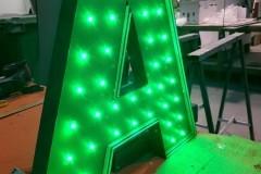 04.a.corporeas-iluminadas-con-leds-pequeños-y-frontal-pmma-verde-con-base-pvc-fresado-y-lacado
